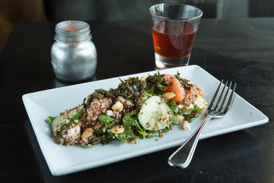 A salad of quinoa with grapefruit, almonds, cucumber, feta, and tea leaves.